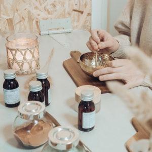 kurssipöytä kynttilä ja naisen kädet tekee luonnonkosmetiikkaa