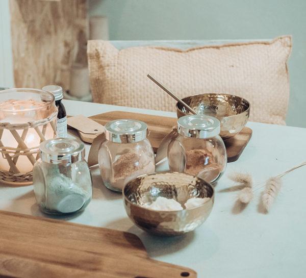 pöytä jossa kaunis kynttilä ja luonnonsavijauheita purkeissa