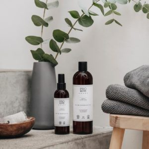 pyykinpesuaine ja hajunpoistaja ruskeissa pulloissa valkoisella etiketillä kauniissa asetelmassa taustalla eukalyptus