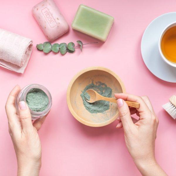 vaaleanpunaisella taustalla luonnonkosmetiikan raaka-aineita pyyherulla eukalyptus ja naisen kädet sekoittaa luonnonsavijauhetta