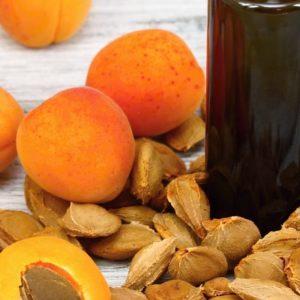 aprikooseja sekä aprikoosin kiviä ja öljypullo