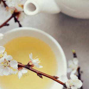 teeöljyä ja teepannu sekä kukkia