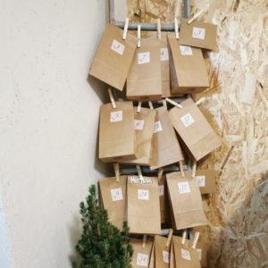 joulukalenteri pussukoita roikkumassa pyykkipojilla tikapuista