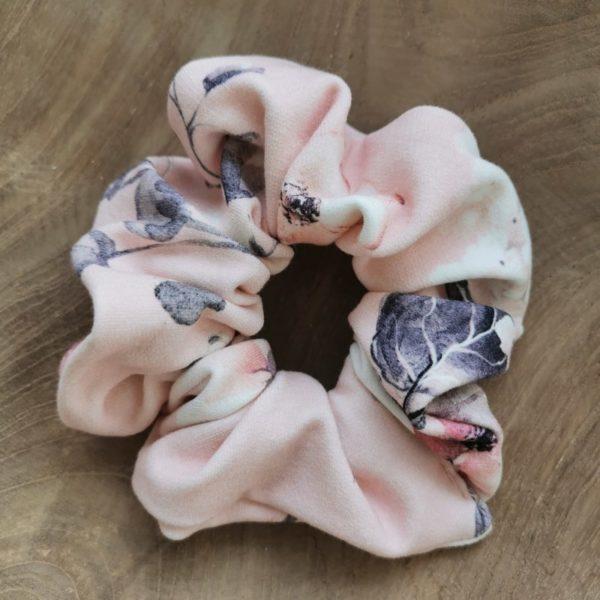 vaaleanpunainen hiusdonitsi kukkakuvioilla puualustan päällä
