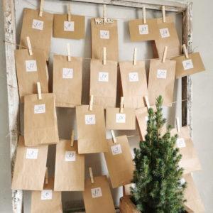 joulukalenterin ekologisia ruskeita paperipusseja ja kirjekuoria roikkumassa vanhoissa ikkunan karmeissa sekä minikuusi